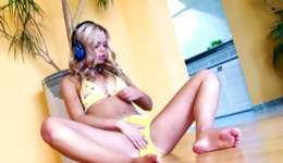 Hot teen blonde is listening to music and flashes her swimming suit